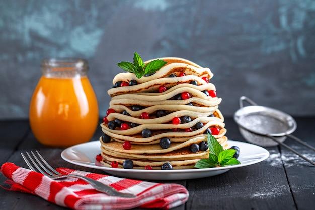 おいしい朝食用の新鮮なベリーと蜂蜜の瓶入りの自家製焼きパンケーキ