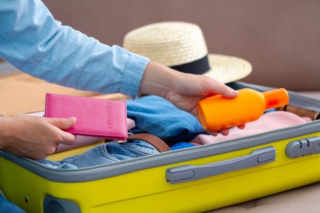 女性旅行者は、新しい旅のために自宅で荷物をまとめます。休日の休暇旅行スーツケース