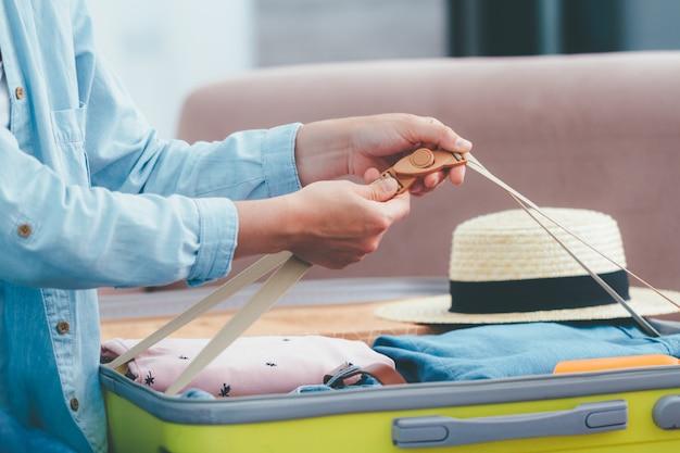 女性旅行者は、新しい旅のために自宅でスーツケースを梱包します。休暇や冒険のための休暇旅行荷物