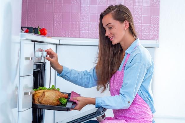 Счастливая домохозяйка в фартуке готовит целую курицу-гриль в духовке на ужин