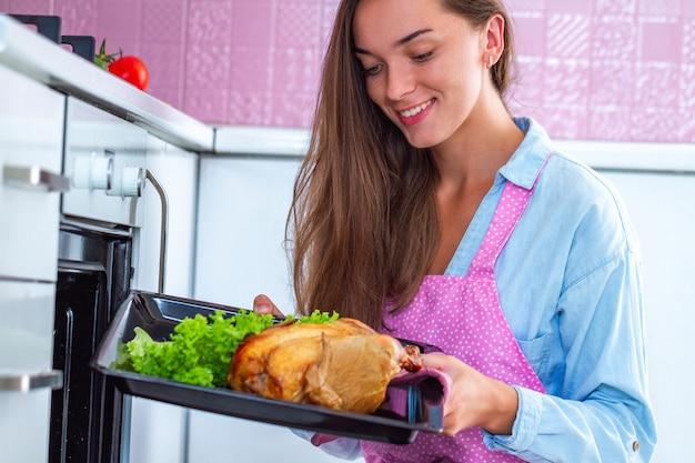 Счастливая усмехаясь привлекательная варя женщина в рисберме печь всю курицу в печи. выпечка утки на ужин в домашних условиях