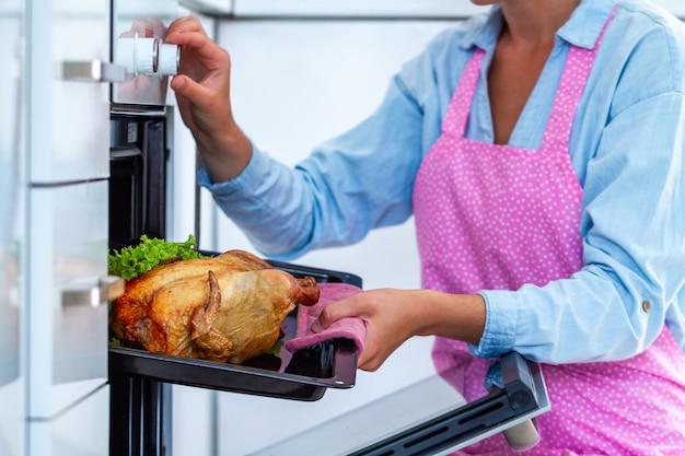 自宅で夕食のオーブンで野菜と鶏肉を焼くエプロンの主婦。休日にアヒルを焼く