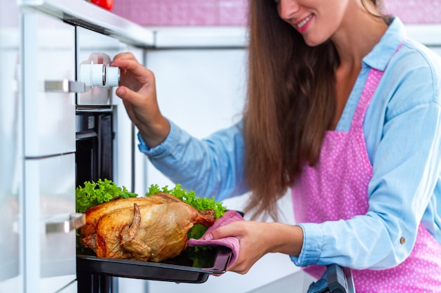 Счастливый домохозяйка в фартук выпечки курица с овощами в духовке. готовим утку на ужин в домашних условиях