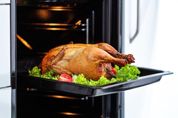 自宅で夕食のためのオーブンで野菜と自家製焼きグリルチキン。休日に鴨を焼く