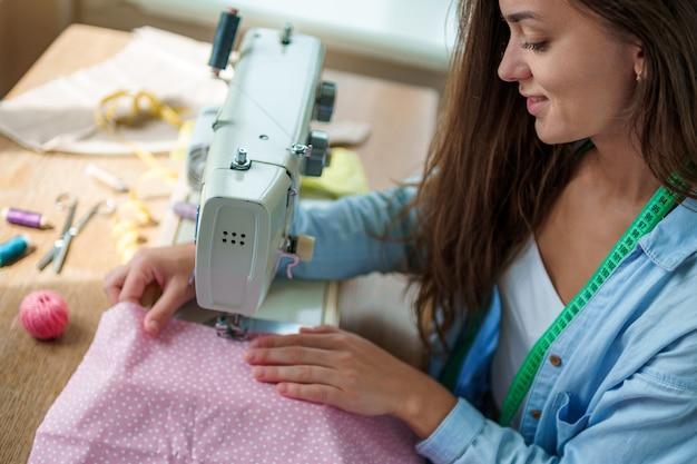 職場での仕立てプロセス中に電動ミシンと異なるミシンアクセサリーで幸せな笑顔の女性の裁縫師
