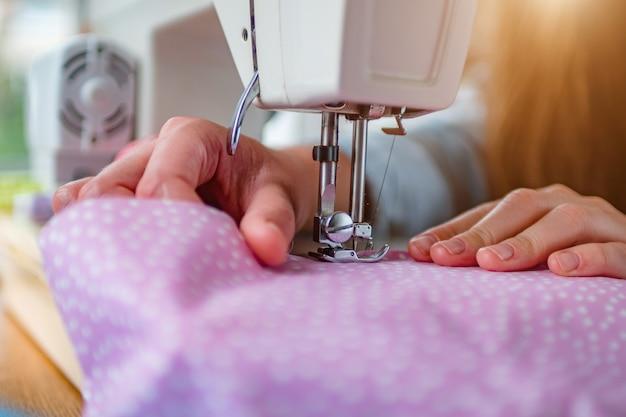 縫製プロセス中に職場でプロの製造機で生地を縫う女性の手がクローズアップ。裁縫師の手がドレス生産のための繊維を保持しています。