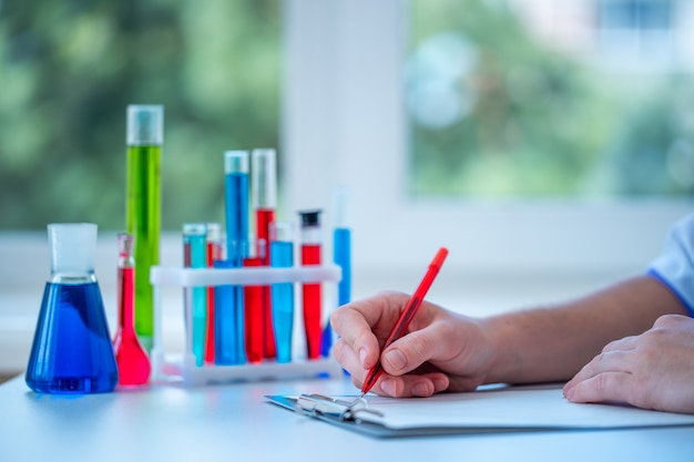 検査室助手は、臨床検査室での研究を行い、研究結果をクリップボードに書き込みます。医学、薬学、美容のコンセプト。テスト用科学ガラス製品