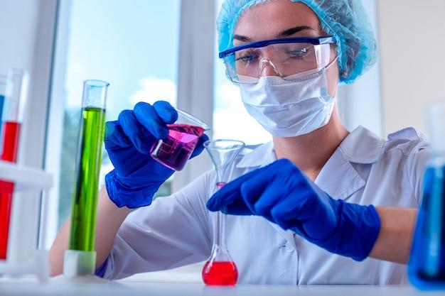 Женский лаборант, использующий различную научную посуду и пробирки для клинических лабораторных исследований и испытаний. концепция медицины, фармации и косметологии.