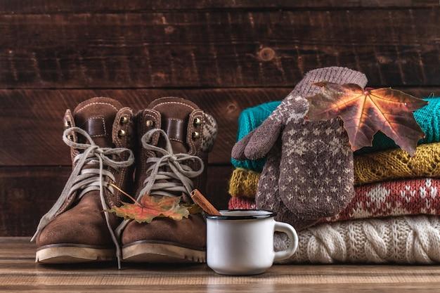 Вязаные, сложенные свитера, теплые варежки, зимние сапоги и осень, кленовые листья на деревянном фоне. зимняя и осенняя одежда. теплая, удобная одежда