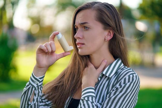喘息の女性は公園で喘息発作と窒息に苦しんでいます。