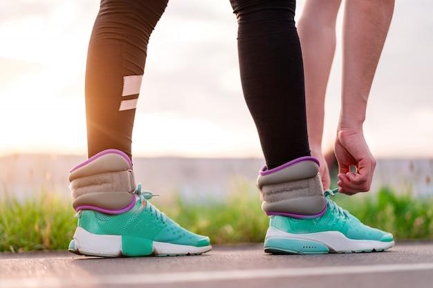 屋外のトレーニング中に重みで歩きながらスニーカーで靴ひもを結ぶ運動の女性。