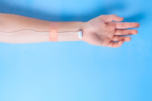 医療注入のようなイヤホンで手。音楽中毒のコンセプト。コピースペース