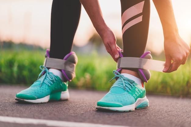 アスレチック女性は、屋外トレーニング中に歩くためのスポーツの重みをつけます。健康的でスポーツライフスタイル。