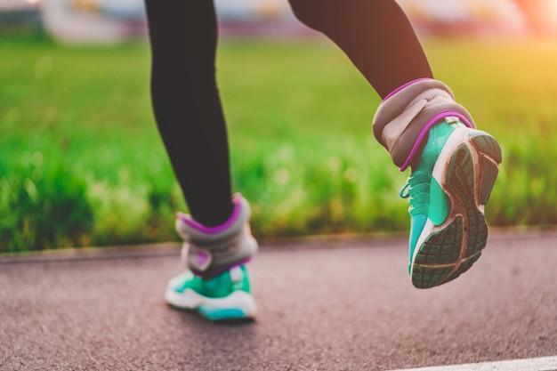 アスレチック女性はスポーツウェイトで歩くと屋外トレーニング中に筋肉と持久力を強化します。健康的でスポーツライフスタイル。