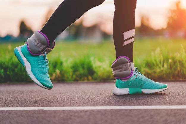 Спортивная (ый) женщина ходит со спортивными весами для укрепления мышц и выносливости во время тренировки на открытом воздухе. здоровый и спортивный образ жизни.