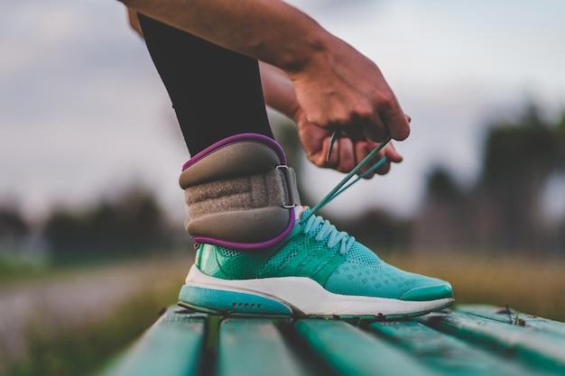 Атлетическая женщина связывая шнурки на тапках пока идущ с весами во время разминки напольной.