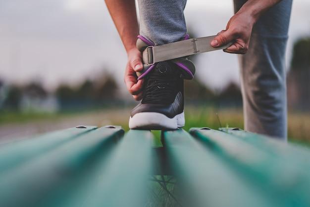 運動男は、屋外のトレーニング中に歩くためのスポーツの重みをつけます。健康的でスポーツライフスタイル。