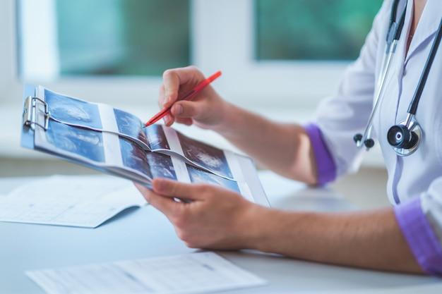 一般開業医は、健康診断と診察中に患者の超音波画像を調べます。医療と医学。病気の診断と治療