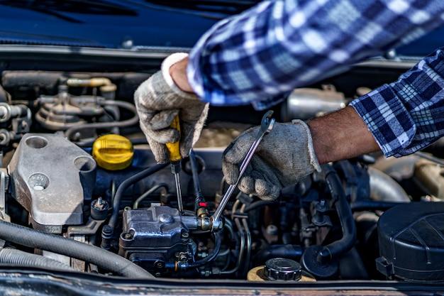 Автомеханик ремонтирует двигатель автомобиля. услуги по ремонту