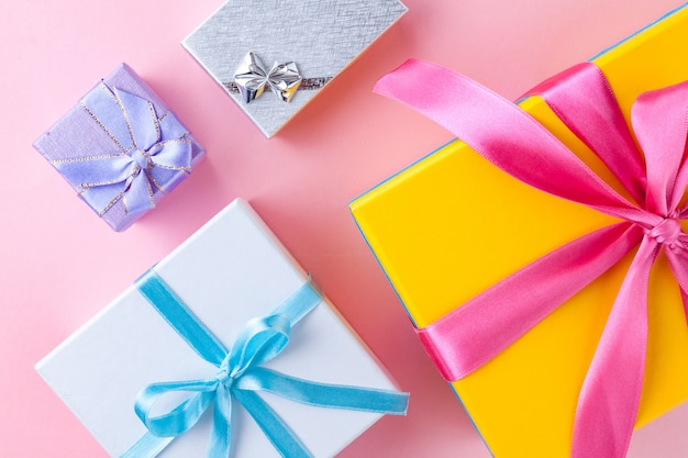 Подарочные коробки на розовом фоне.