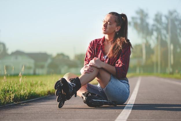 ローラーブレードとインラインスケート中に落ちた後あざを持っている女性の膝を負傷
