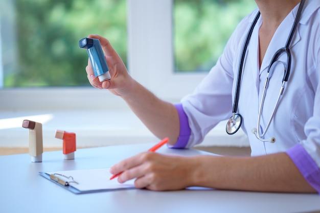 医師が医療相談と検査中に喘息患者に喘息吸入器の処方箋を書く