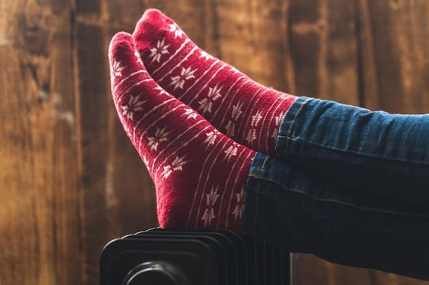 クリスマスの女性の足、ヒーターの暖かい、冬の靴下。冬は寒く、夜は暖かくしてください。暖房シーズン