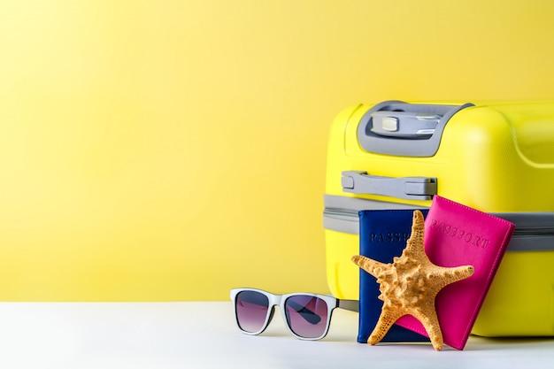 明るい黄色の旅行スーツケース、パスポート、サングラス、ヒトデ。旅行のコンセプト。コピースペース