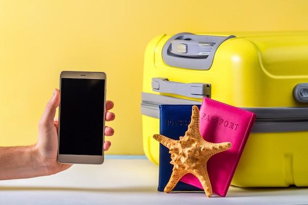 オンライン予約。インターネットでチケットやホテルを予約する。明るい黄色の旅行スーツケース、パスポート、ヒトデ。旅行のコンセプト。レジャー、休暇
