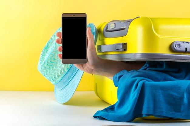 Бронирование онлайн. бронирование билетов и отелей в интернете. туристический чемодан с одеждой на ярком. концепция путешествия. отдых, отпуск