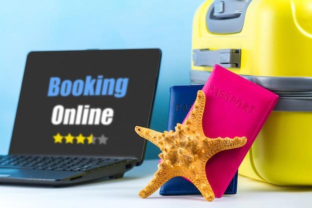 オンライン予約。オンラインでチケットを注文し、ホテルを予約します。明るい黄色の旅行スーツケース、パスポート、ラップトップ、貝殻。旅行のコンセプト