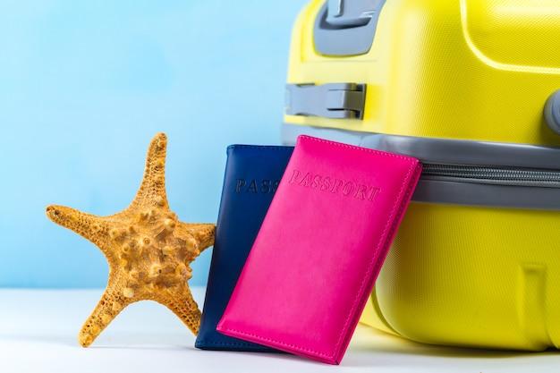 明るい黄色の旅行スーツケース、パスポート、ヒトデ。旅行のコンセプト。