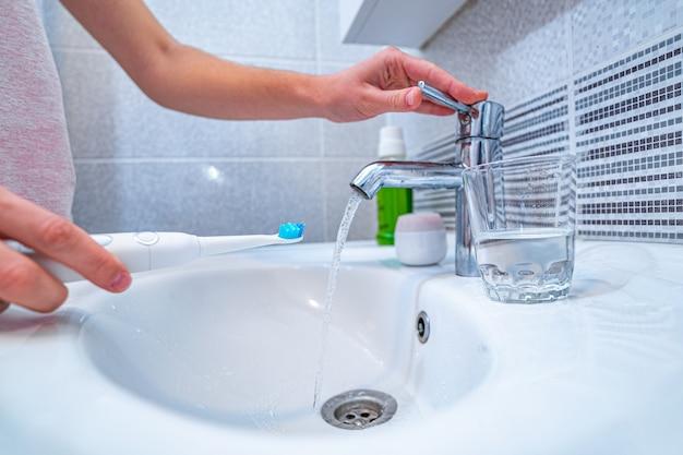 人は超音波歯ブラシで歯を磨き、自宅の浴室で歯を磨き、新鮮な呼吸のために歯科製品を使用する