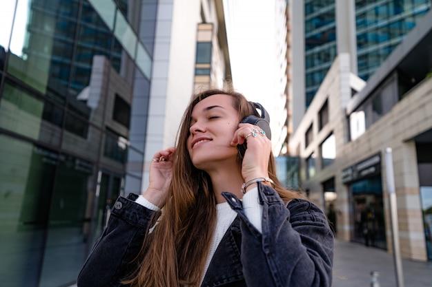 Стильная модная счастливая хипстерская женщина-подросток наслаждается музыкой в беспроводных наушниках, гуляя по городу. любитель музыки