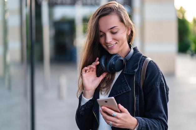 Счастливая женщина наслаждается музыкой в беспроводных наушниках во время прогулки по городу