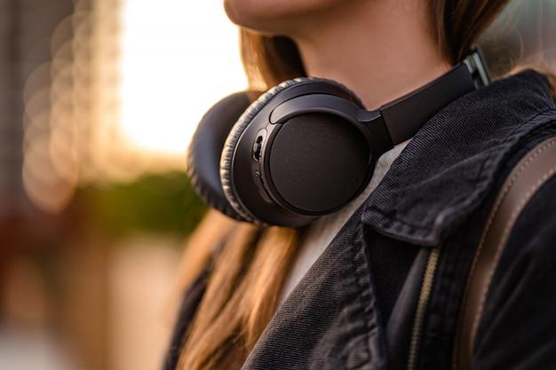 Стильный случайный модный хипстер студент женщина подросток с черными беспроводными наушниками во время прогулки по городу. любитель музыки любит слушать музыку