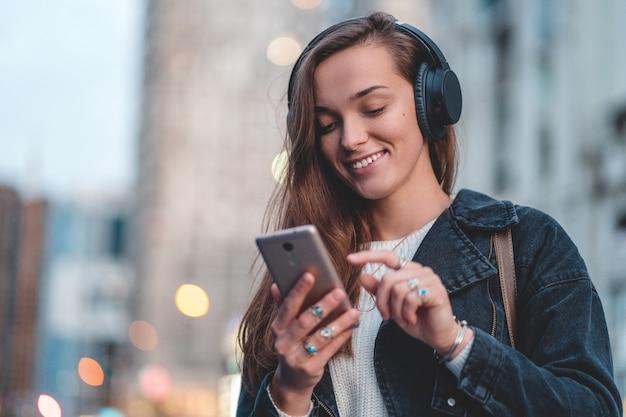 Подросток наслаждается и слушает музыку в черных беспроводных наушниках во время прогулки по городу
