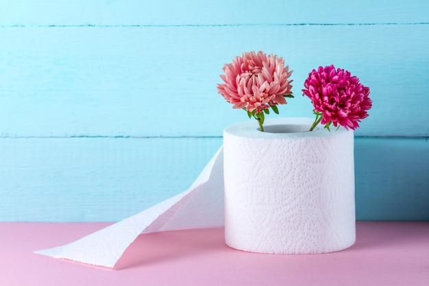 ピンクのテーブルの上の香りのトイレットペーパーロールと花。においのあるトイレットペーパー。衛生コンセプト。トイレットペーパーのコンセプト