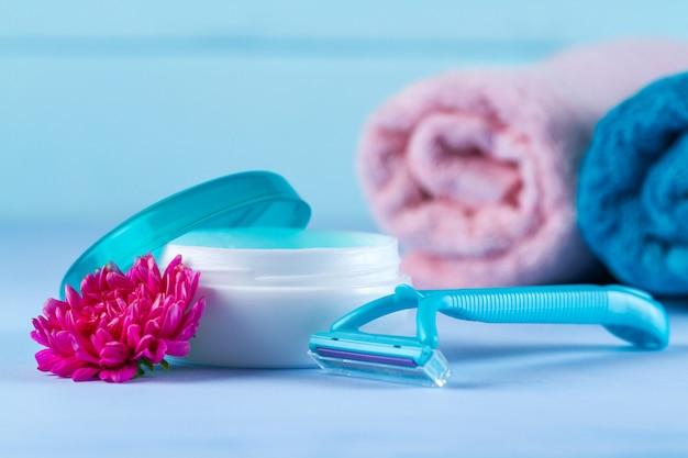 クリーム、女性用の剃毛かみそり、タオル、ピンクの花。脱毛。不要な毛の除去。
