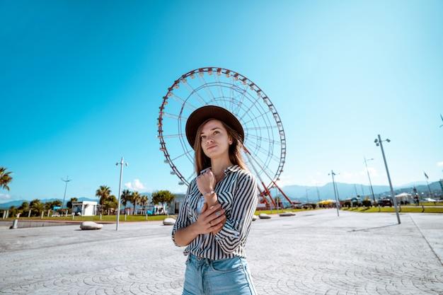 Женщина-путешественница в шляпе гуляет в порту у колеса обозрения в курортном городе батуми, грузия во время отпуска