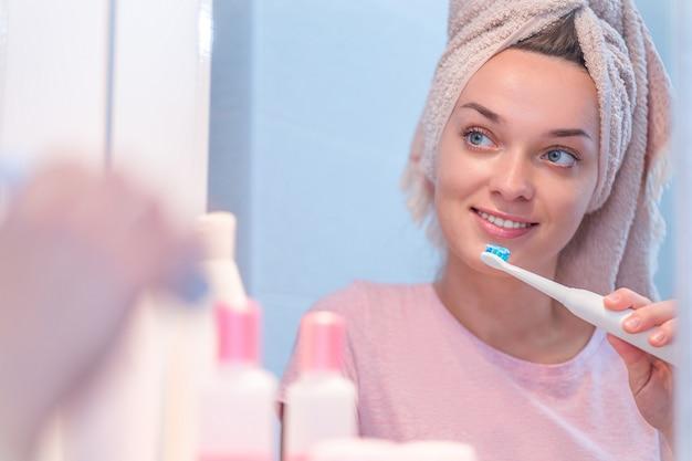 幸せな健康な女性は自宅の浴室で超音波電動歯ブラシを使用して歯を磨く