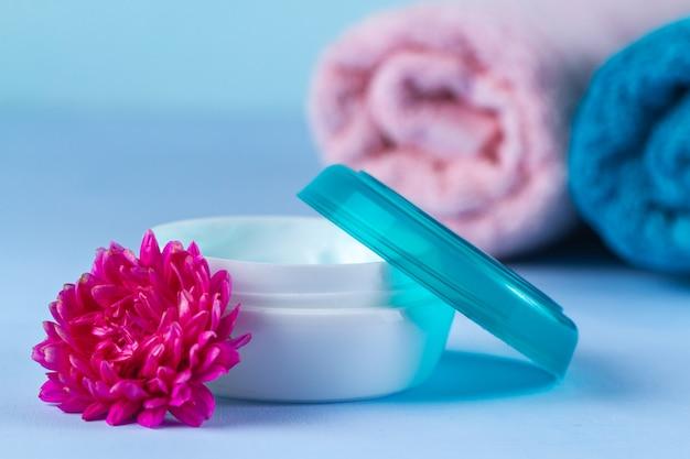 肌に潤いを与えるクリーム、ピンクの花、タオル。乾燥肌の除去。スキンケア。