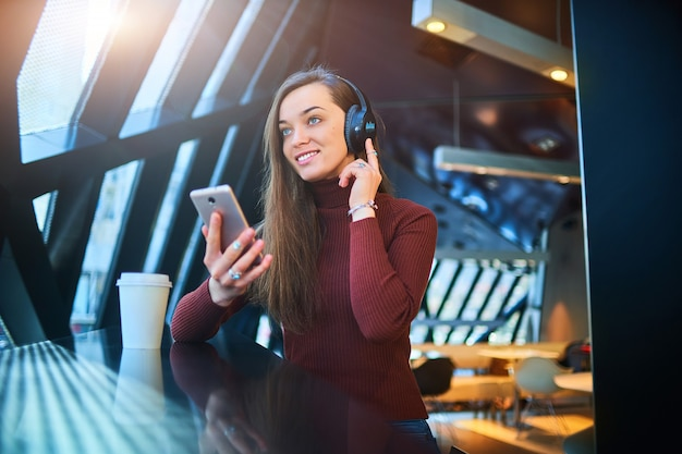 Счастливая вскользь молодая женщина с черными беспроволочными наушниками и телефоном наслаждаясь музыкой в кафе.