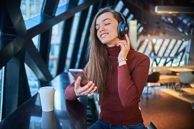 Вскользь молодая счастливая радостная женщина любителя музыки с черными беспроволочными наушниками наслаждаясь музыкой.