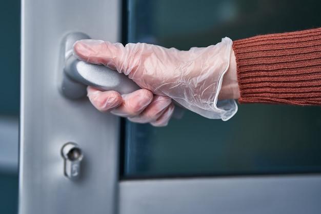 透明な保護手袋を着用している人は、インフルエンザのコビド発生と感染性コロナウイルスの流行中にハンドルを握ります。ウイルス、細菌、細菌に対する健康保護