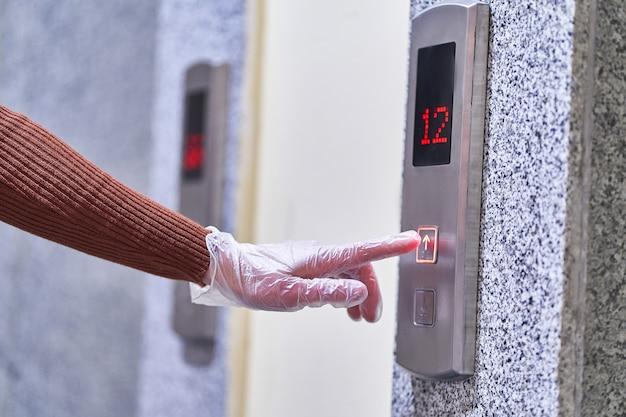 透明な保護手袋を着用している人が、インフルエンザコビッドウイルスの発生、コロナウイルスの流行および感染症の間にリフトボタンを押す