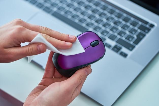 オフィスワーカーは抗菌性ウェットワイプで作業中のマウスを消毒およびクリーニングして、コロナウイルスの発生を防ぎます