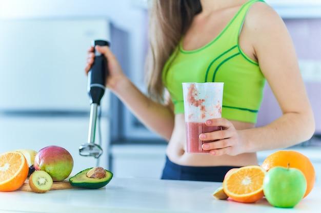 スポーツウェアのフィットネス女性は、自宅のキッチンでハンドブレンダーを使用して新鮮なフルーツのスムージーを準備します。