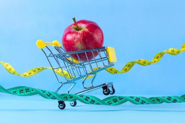 ショッピングカートと測定テープで新鮮なリンゴ。ダイエットのコンセプト。体調を整え、スポーツを行い、余分なキロを失うことを計画する