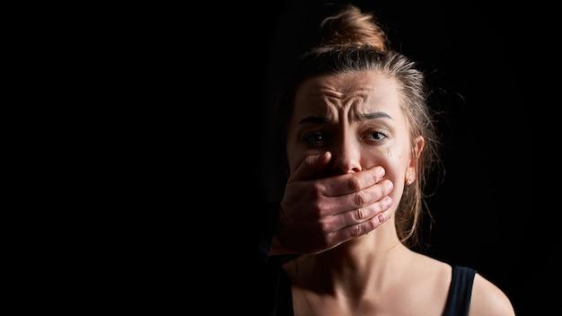 女性の家庭内暴力に苦しむ恐怖で不幸な泣いている女性の犠牲者を強調